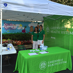 Two representatives stand at the booth for Greenville Health System
