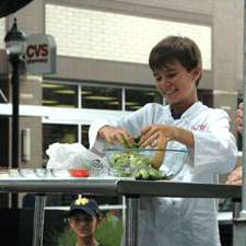 A youth in a chef's coat shreds greens into a bowl